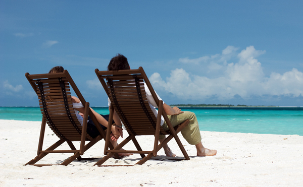 Young happy couple relaxing at tropical white sand beach